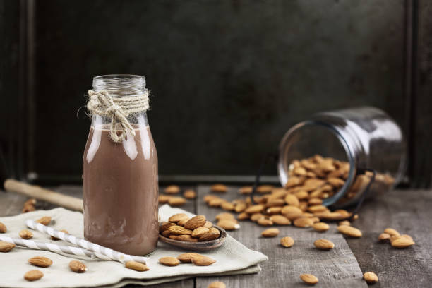 Organic Chocolate Almond Milk with Nuts Organic chocolate  almond milk in a glass bottle with whole almonds spilled over a rustic wooden table. chocolate milk stock pictures, royalty-free photos & images