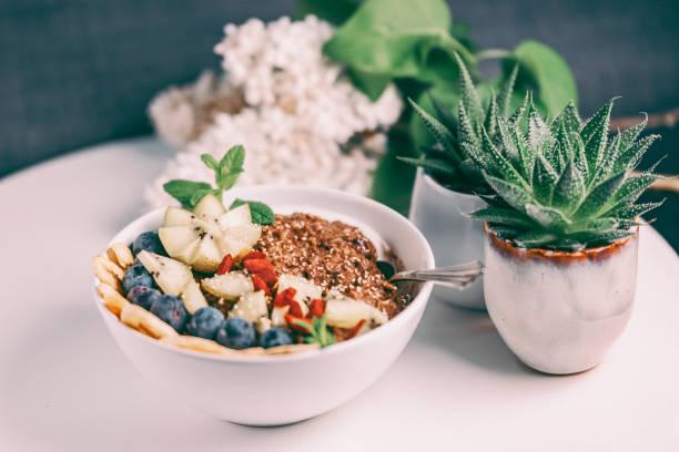 Bio Schokolade und Buchweizen Porridge Schale gekrönt mit Wolfbeeren, Banane, Heidelbeeren, Kiwi und geknallt Amaranth – Foto
