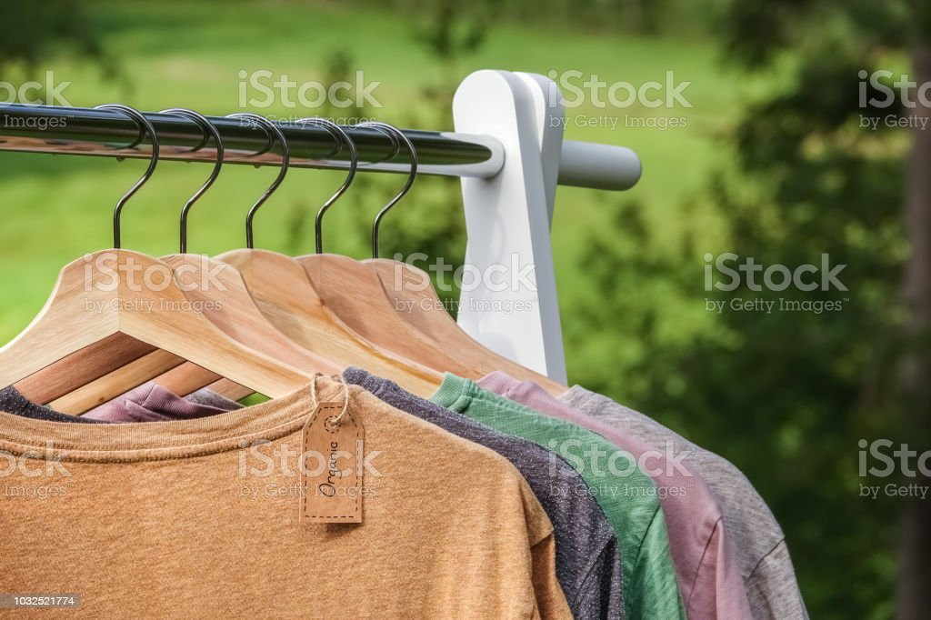 Organic clothes, t-shirts hanging on wooden hangers with green forest, nature in background. royalty-free stock photo