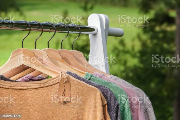 Organic clothes tshirts hanging on wooden hangers with green forest picture id1032521774?b=1&k=6&m=1032521774&s=612x612&h=zccpej8woyju0pdmhnript9b f3uxezrj79npaghq3w=