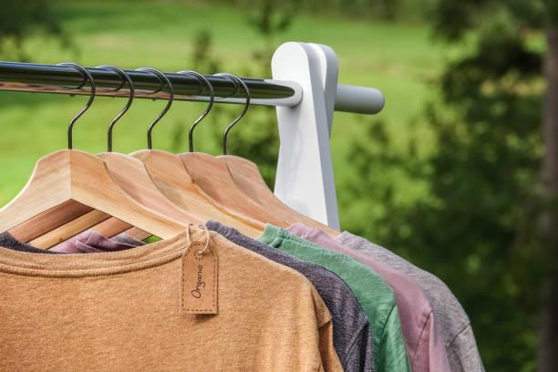 organiczne ubrania, t-shirty wiszące na drewnianych wieszakach z zielonym lasem, natura w tle. - odzież zdjęcia i obrazy z banku zdjęć