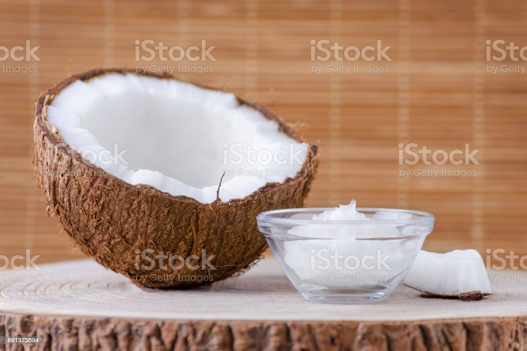 organic coconut oil in a glass bowl and coconut on natural brown background stock photo
