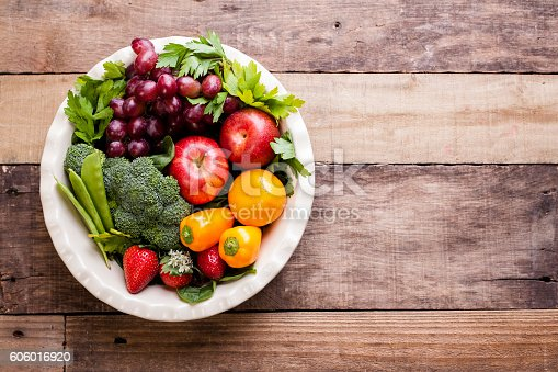 Eat the rainbow!  Various, colorful fruits and vegetables: grapes, parsley, brocolli, apples, strawberries, tangerines, peppers, snow peas in white bowl on rustic wooden table.  Copyspace.  Healthy lifestyles, dieting, healthy eating.  No people.  Directly above, high angle view.  Fruit backgrounds.