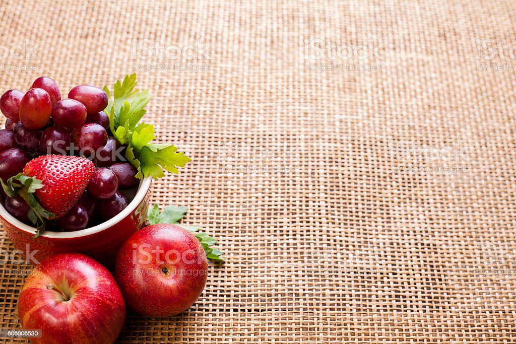 Organic colorful strawberries, grapes, apples on textured surface. stock photo