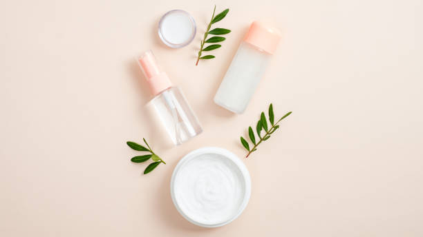 Organic cosmetic bottle containers and jar with white face cream on beige background with green herbal leaves. Creative layout, minimal flat lay style composition. Natural beauty product concept.