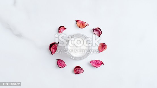 1128479585 istock photo Organic cosmetic cream jar and red flower petals on marble background. Top view, flat lay. Natural beauty product. Skincare and body care concept 1199956472