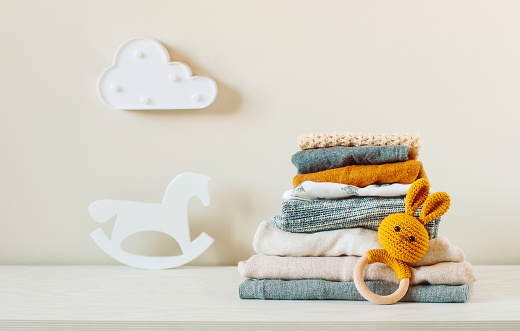 Organic cotton baby clothes on the shelf in the kids room.