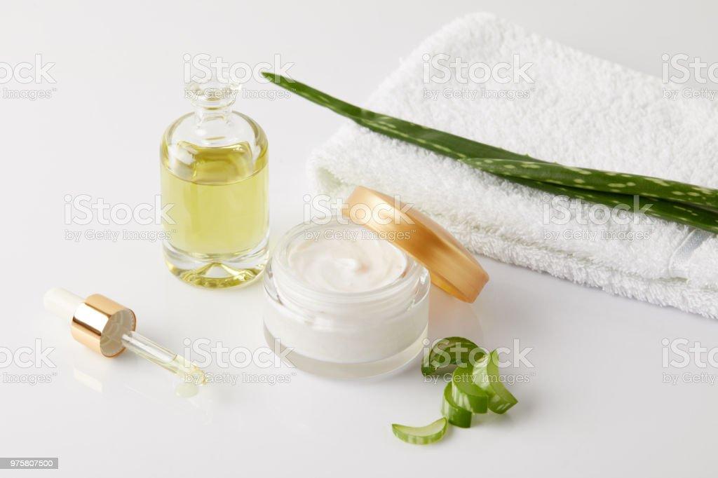 Bio-Creme und Parfüm, Pipette, Handtuch und Aloe Vera Scheiben und Blatt auf weiße Fläche - Lizenzfrei Aloe Stock-Foto