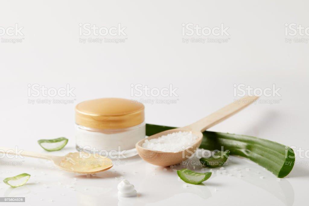 Bio Creme in Container, Löffel mit Aloe-Vera-Saft, Salz, Aloe Vera Blatt und Scheiben auf weiße Fläche - Lizenzfrei Aloe Stock-Foto