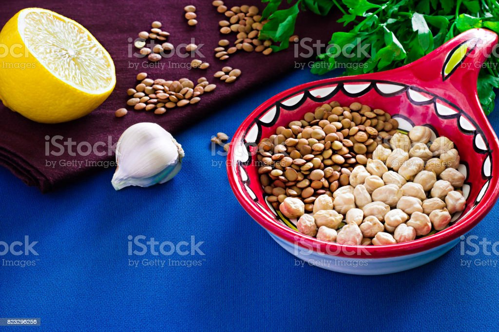 Organic diet food for healthy nutrition. Ingredients for cooking vegetarian soup or stew. Chickpea, lentil, lemon, parsley and garlic background stock photo