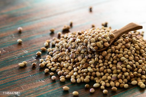 Organic Dried coriander seeds (Coriandrum sativum) with spoon on colored rustic background. Healthy eating, Indian spice, flavoring, vitamin.
