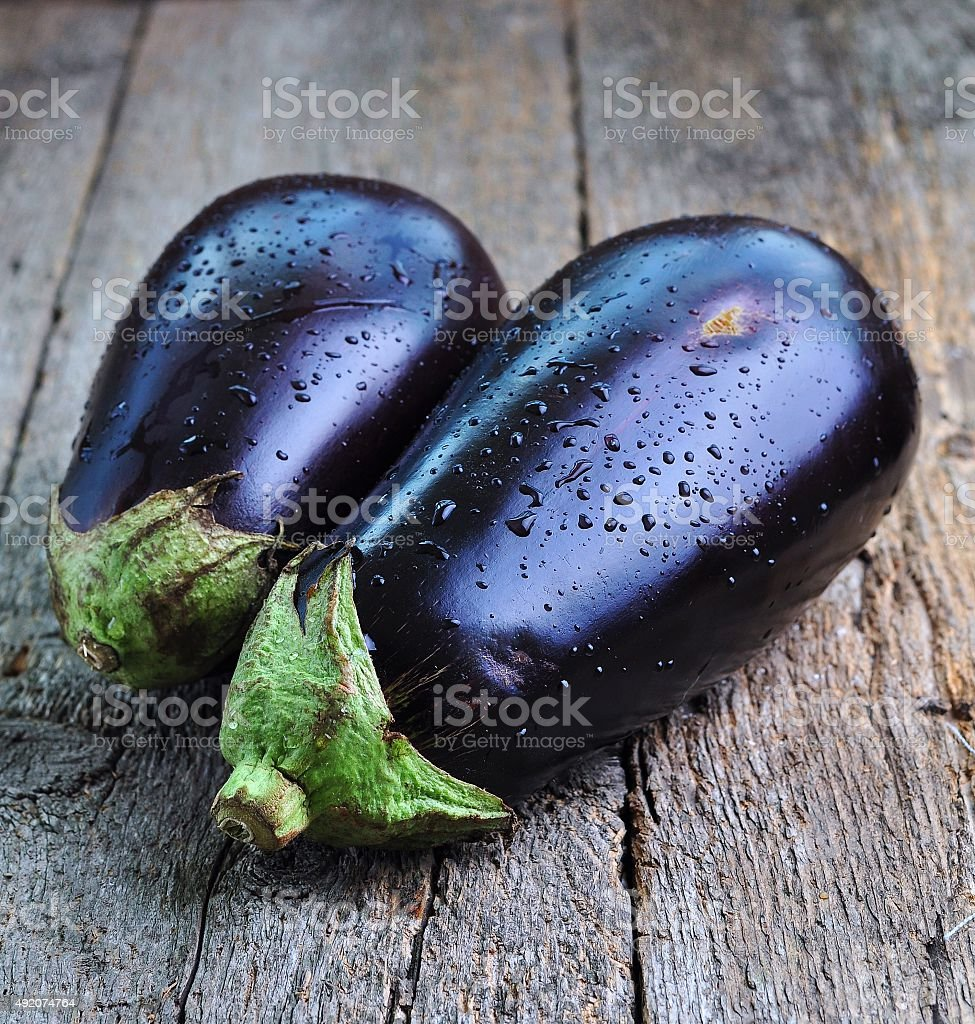 organic eggplants on a wooden background stock photo