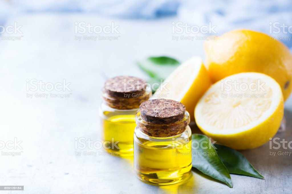 Organic essential lemon oil with green leaves and fruit stock photo