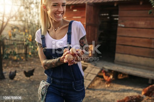 Young smiling woman holding hands full of eggs.