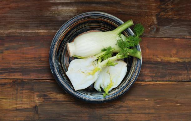 bio fenchelknollen mit salz und pfeffer bereit, über hölzerne hintergrund zu kochen. isoalted. - fenchel überbacken stock-fotos und bilder