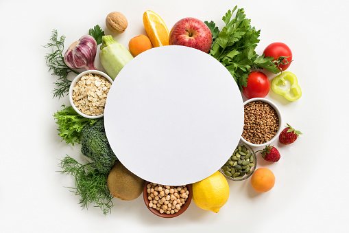 Organic Food Background - assorted vegan food isolated on white, creative layout with round copy space. Healthy clean eating or diet concept.