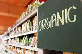 istock Organic food signage on modern supermarket grocery aisle 831694504