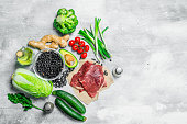 Organic food. Variety of healthy food with raw beef meat . On a rustic background.