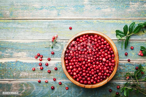 istock Organic fresh cowberry (lingonberry, partridgeberry, foxberry) in wooden bowl on rustic vintage table top view. 838308664