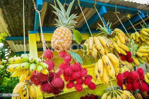This is a horizontal, color royalty free stock photograph of fresh fruit at a farmer's market stand in rural Kona, Hawaii. Tropical star fruit, pineapple, bananas and rambutan are set out for sale on a display. Photographed with a Nikon D800 DSLR.