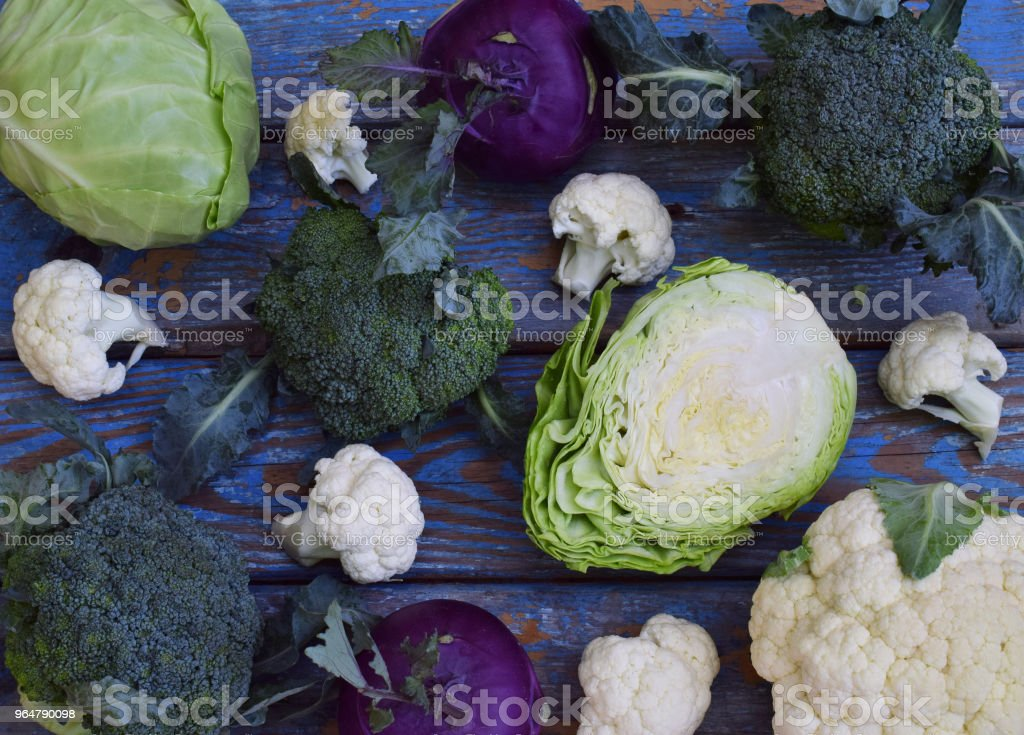 Organic fresh summer vegetables - different varieties of cabbages on wooden background. Cauliflower, kohlrabi, broccoli, white head cabbage. Raw food royalty-free stock photo