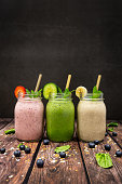 A Strawberry, blueberry and banana smoothie.  A cucumber, spinach, Lime and avocado smoothie.  A Banana and pineapple smoothie.  All with flax seed, chia seed and oat smoothie in drinking jars photographed on a wooden table against a dark background.  Also pictured is bamboo eco straws and sprigs of mint.