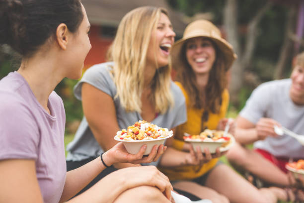 organic fruit stand - owner eating and enjoying selection of organic fruit together with friends - hawaiian ethnicity stock photos and pictures
