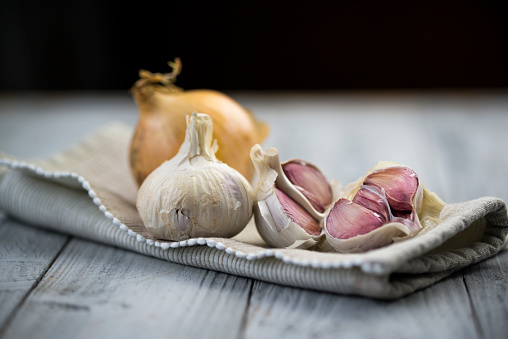 Organic garlic and onion on wooden background