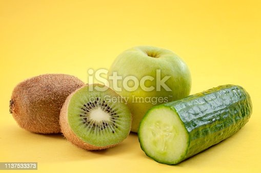 istock Organic green fruits and vegetables concept with close up on cucumber, apple and kiwi isolated on minimalist yellow background 1137533373