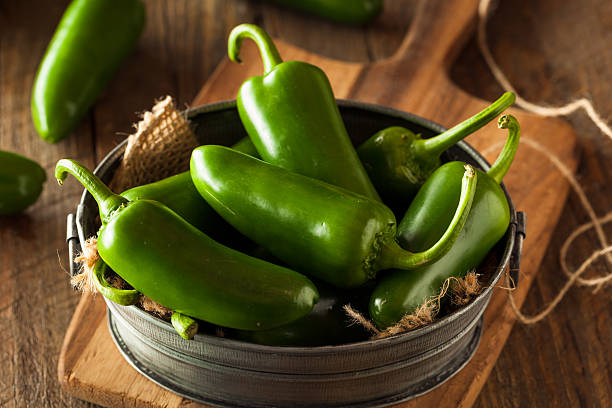 Organic Green Jalapeno Peppers Organic Green Jalapeno Peppers in a Bowl jalapeno pepper stock pictures, royalty-free photos & images