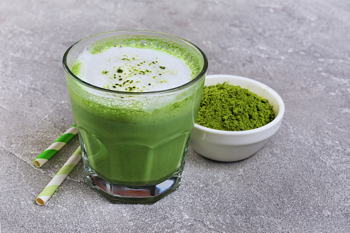 Organic green matcha tea latte in glass and powder in white bowl