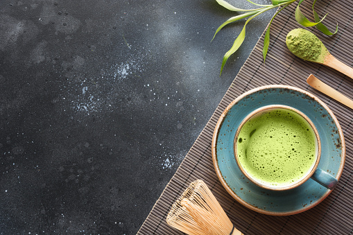 Organic green matcha tea on black table. Top view. Space for text.