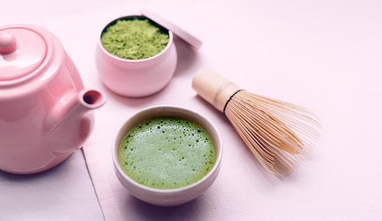 Fresh organic matcha tea powder and drink with bowl and Chasen bamboo whisk.