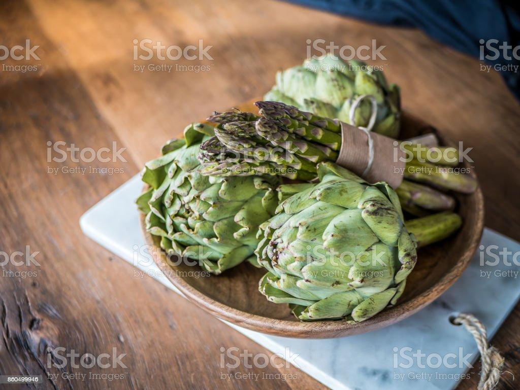 Organic green vegetables food in wood bowl. Asparagus and artichoke on wooden background. stock photo