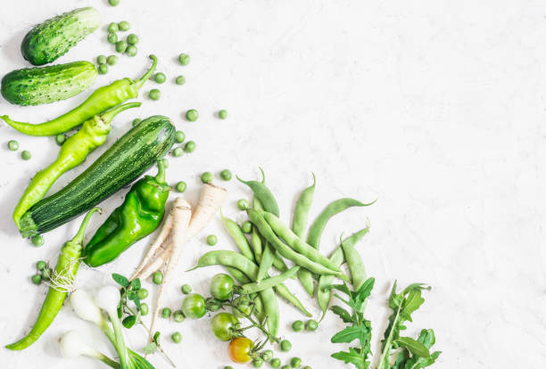 Organic green vegetables on a white background. Cooking ingredients - cucumbers, zucchini, peppers, onions, parsnip, green onions, tomatoes, green peas, beans. Free space for text, top view. Flat lay stock photo