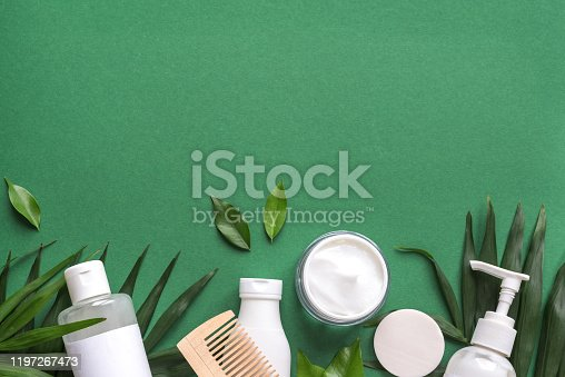 Organic Hair Care products with green leaves on green background, trendy layout, eco beauty and healthy lifestyle concept.