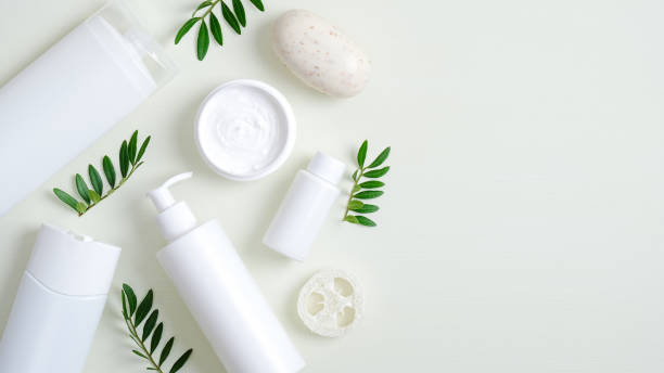 Organic herbal cosmetic products on green background. Top view beauty spa cosmetic bottle packaging, hand cream, lotion, bath sponge, natural soap and green leaves. Minimalist beauty product mockups