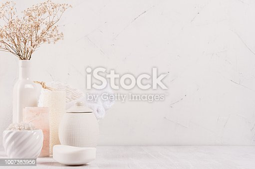 istock Organic homemade white cosmetics products in different ceramics bowls, pink salt and small dried flowers  on white wooden background, border. 1007383956