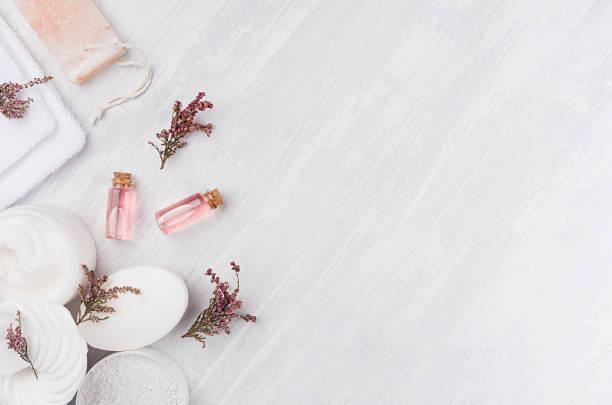 hausgemachte weiße biokosmetik mit rosa blüten und massageöl auf weißen holzplatte, draufsicht, grenze. - blumen make up stock-fotos und bilder