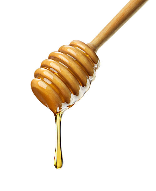 Organic Honey with wooden dipper against white Close-up of organic honey dripping off a wooden honey dipper against a white background. Shot with H4D-40. burwellphotography stock pictures, royalty-free photos & images