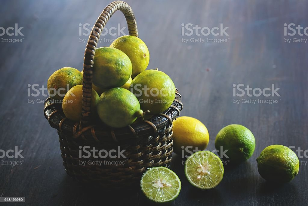 Organic Key Limes in a basket, selective focus stock photo