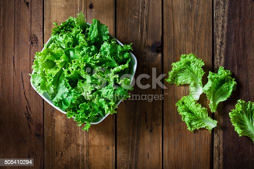 Organic lettuce bowl shot from above on rustic wood table.  DSRL studio photo taken with Canon EOS 5D Mk II and Canon EF 70-200mm f/2.8L IS II USM Telephoto Zoom Lens