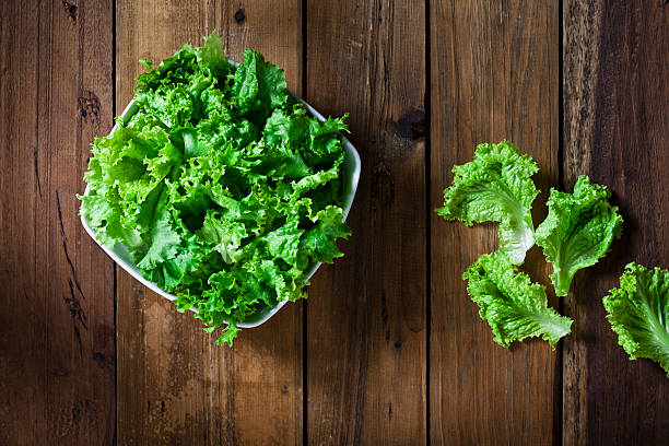 organic lettuce bowl shot from above on rustic wood table - lettuce stock photos and pictures