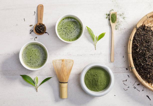 ekologiskt matcha grönt te pulver i skål med tråd visp och grönt te blad på vitt stenbord, ekologisk produkt från naturen för friska med traditionell stil - spirulinabakterie bildbanksfoton och bilder