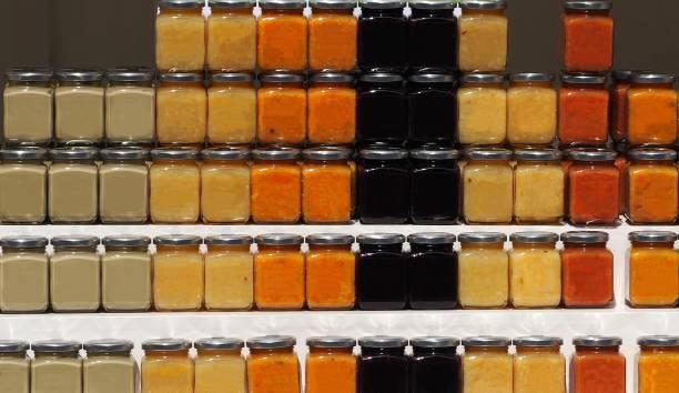 bio-mediterrane marmelade gläser mit neuen geschmacksrichtungen auf einem regal. pistazien, zitrone, blut-orange, schwarze maulbeere, zitrone mit ingwer, orangen mit pistazien - ingwermarmelade stock-fotos und bilder