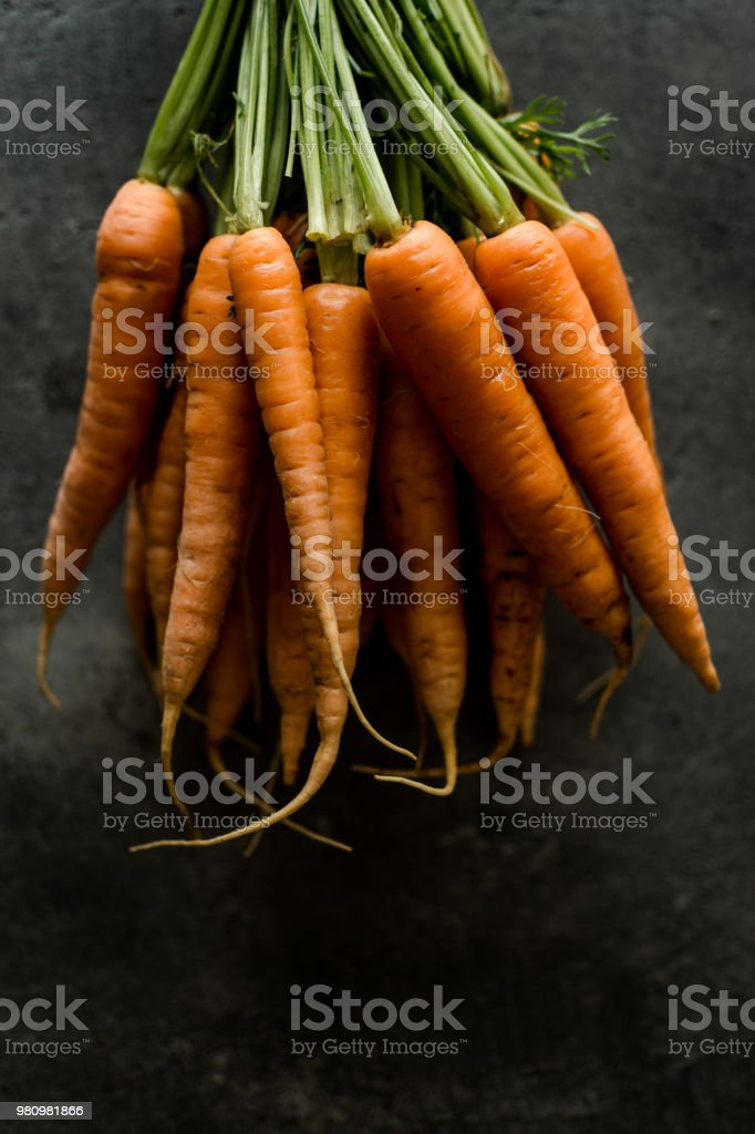 Organic Nantes Carrots on Rustic Dark Background. Fresh Superfood...