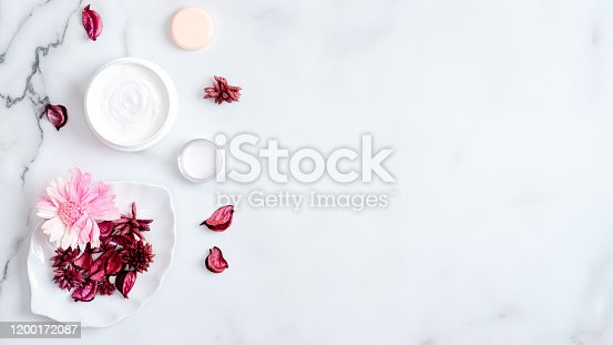 1128479585 istock photo SPA organic natural cosmetic cream containers with pink flower petals on marble background. Skin care, beauty, SPA concept. Flat lay, top view, copy space 1200172087