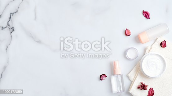 1128479585 istock photo SPA organic natural cosmetic lotion bottles and cream jars on marble background with pink flower petals. Top view bath body cream and herbal bath oil. Skincare, beauty, SPA concept 1200172059