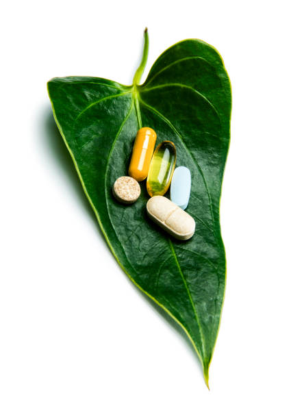 Organic Natural Supplements Pills on Green Leaf stock photo