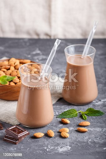Organic non dairy almond chocolate milk in glass and wooden plate with almond nuts on a black concrete background. Vegan healthy food concept, close up, side view.